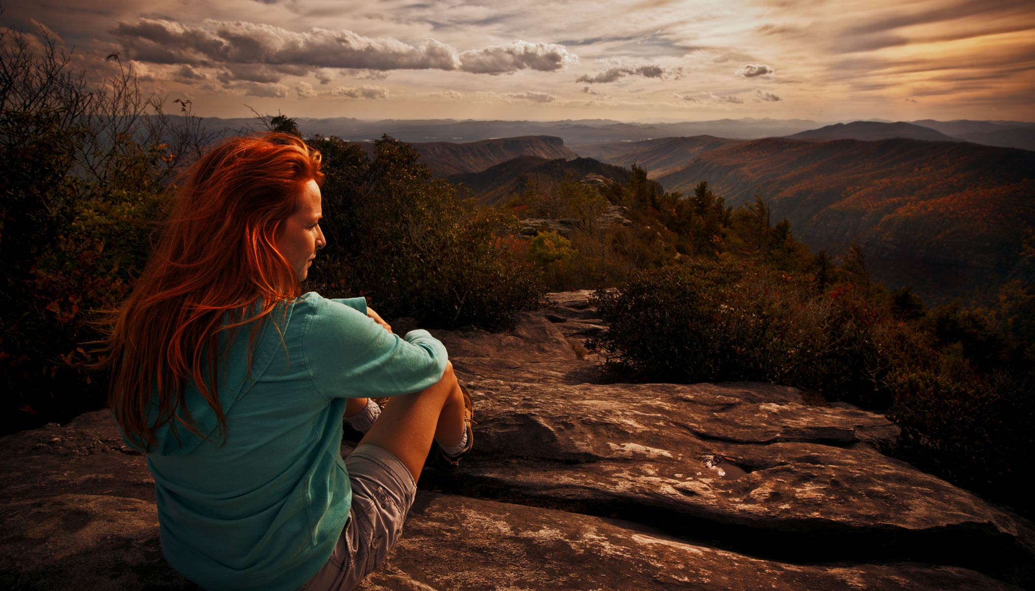 Woman Sitting On Rock In Mountains